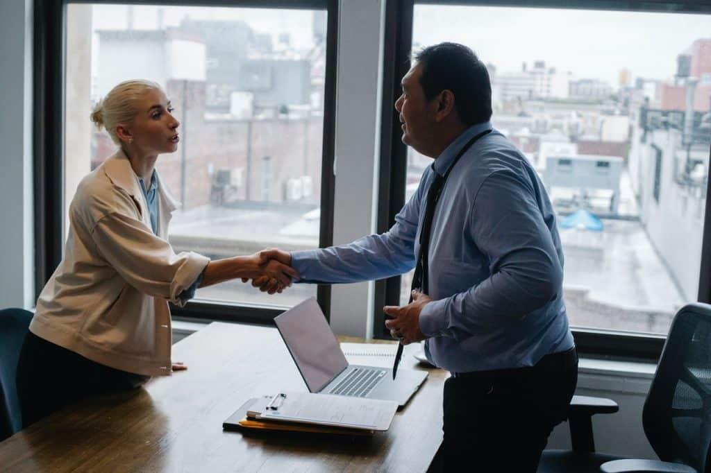Homem e mulher de roupas sociais apertando as mãos dentro de um escritório.