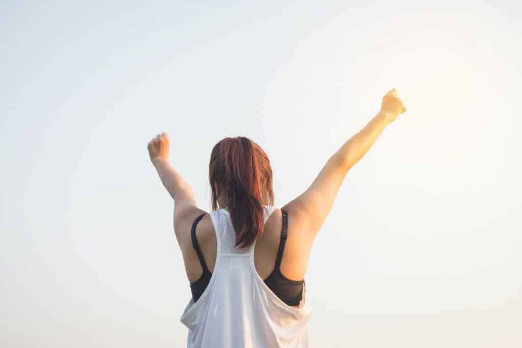 Mulher de braços erguidos. O cenário é de céu limpo.