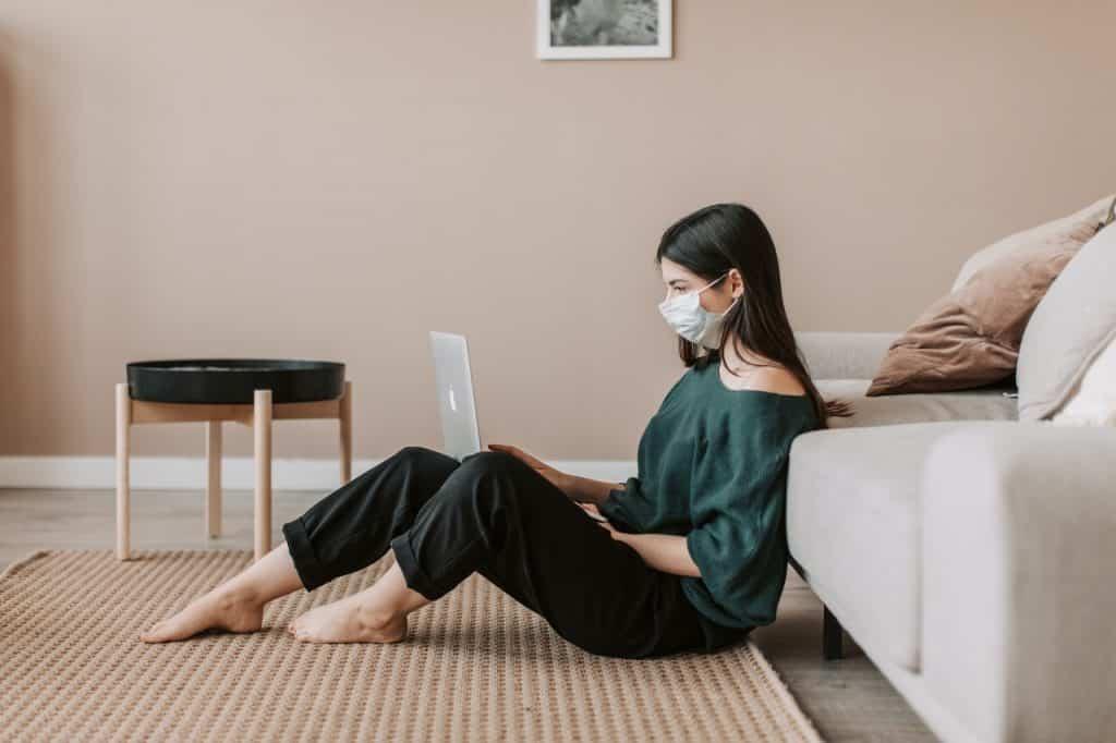 Menina de máscara descartável sentada no chão da sala mexendo no notebook.