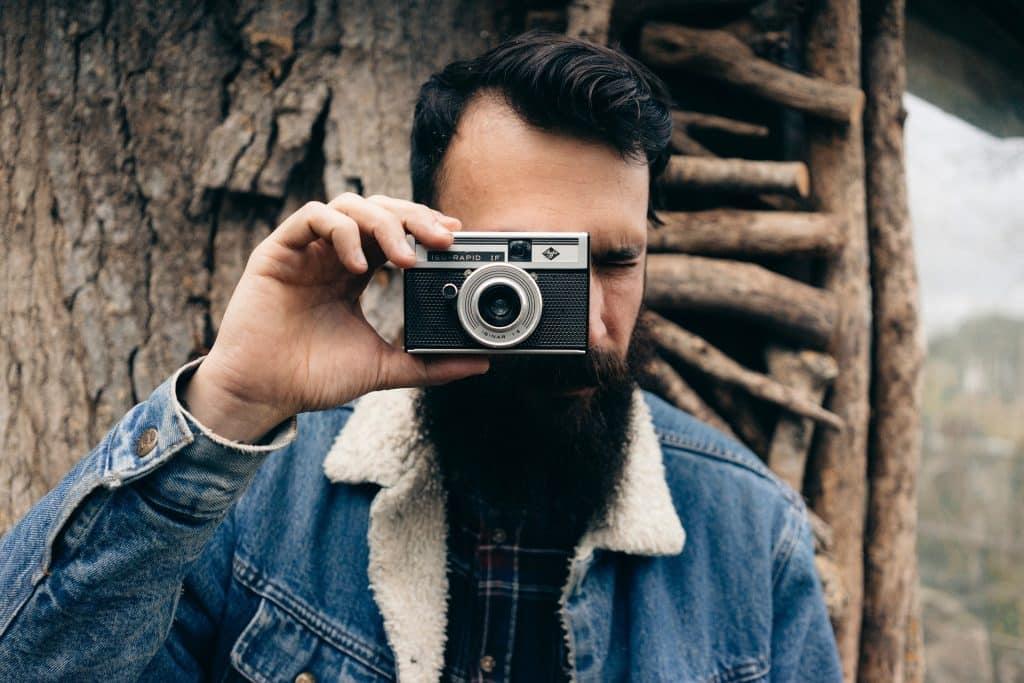 Imagem de um jovem de cabelos escuros, barba e bigode. Ele está encostado em uma árvore, usa uma jaqueta jeans com pele de carneiro e segura em uma das suas mãos uma máquina fotográfica.