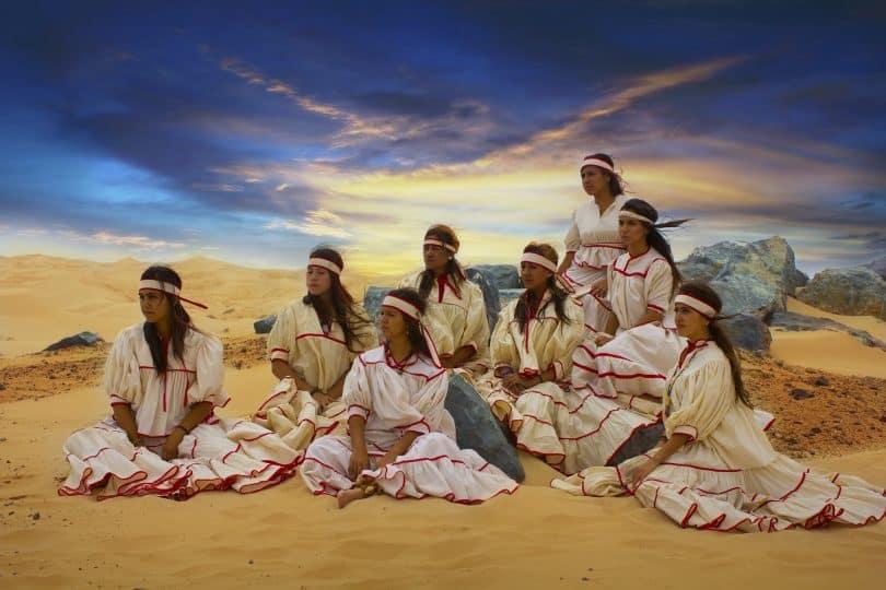 Imagem de oito mulheres indígenas em um terreiro dentro de sua tribo. Elas usam cabelos longos e soltos e uma faixa decorativa na cabeça. Também usam vestidos longos, na cor bege com detalhes na cor vermelha. Todos os vestidos são iguais.