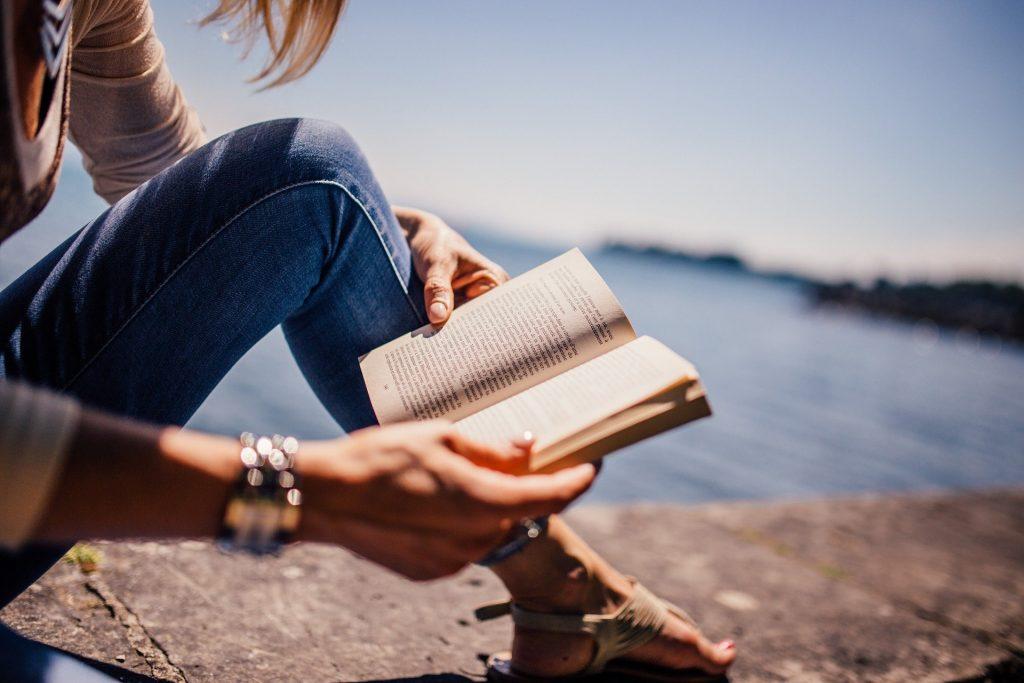 Imagem de uma mulher sentada em uma mureta próximo a um lago de águas cristalinas. Ela usa uma calças jeans, pulseiras prateadas e está segundo um livro em suas mãos, aberto onde faz uma leitura.