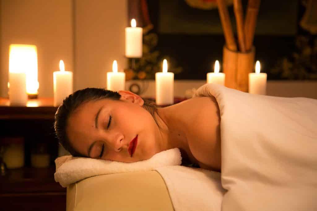 Imagem de uma mulher deitada em uma maca. Ela acabou de receber uma sessão de massagem.  Agora ela está descansando com o rosto sobre uma toalha branca. Ao fundo seis velas brancas e acesas decoram o ambiente.