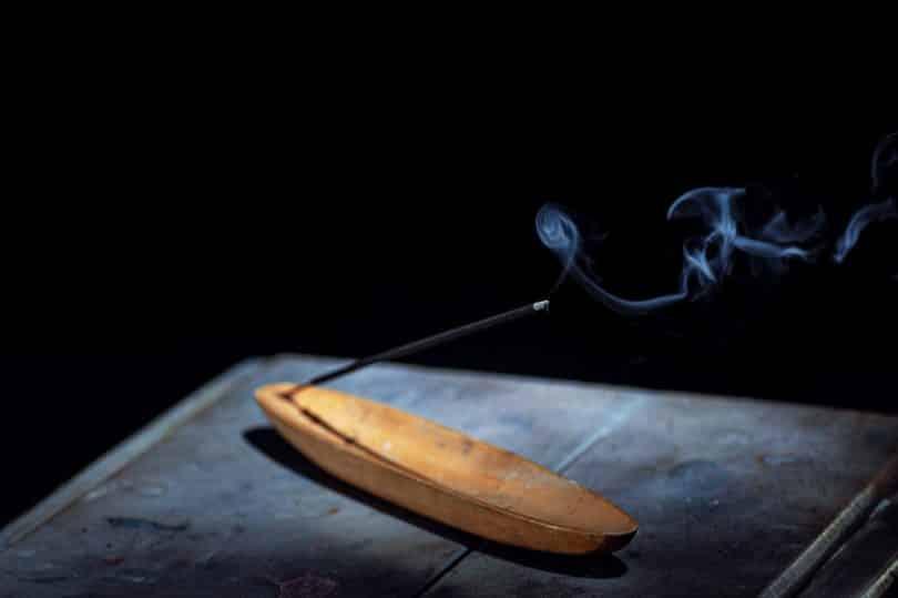 Imagem de fundo preto e em destaque uma mesa de madeira e sobre ela um incenso de citronela sendo queimando. Ele está disposto em um incensário de madeira na cor bege claro.