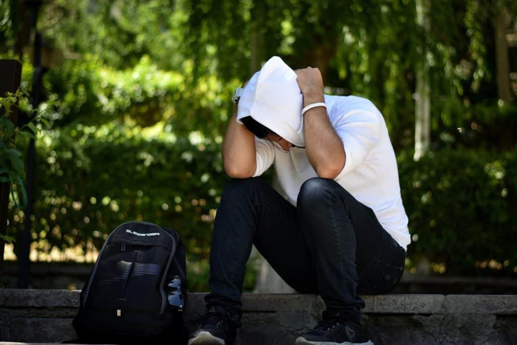 Imagem de  um jovem sentando na beira da calçada. Ele está com as duas mãos sobre a sua cabeça, ele está estressado e com dores. Ao lado dele uma mochila. Ele usa uma blusa com touca e uma calça jeans.