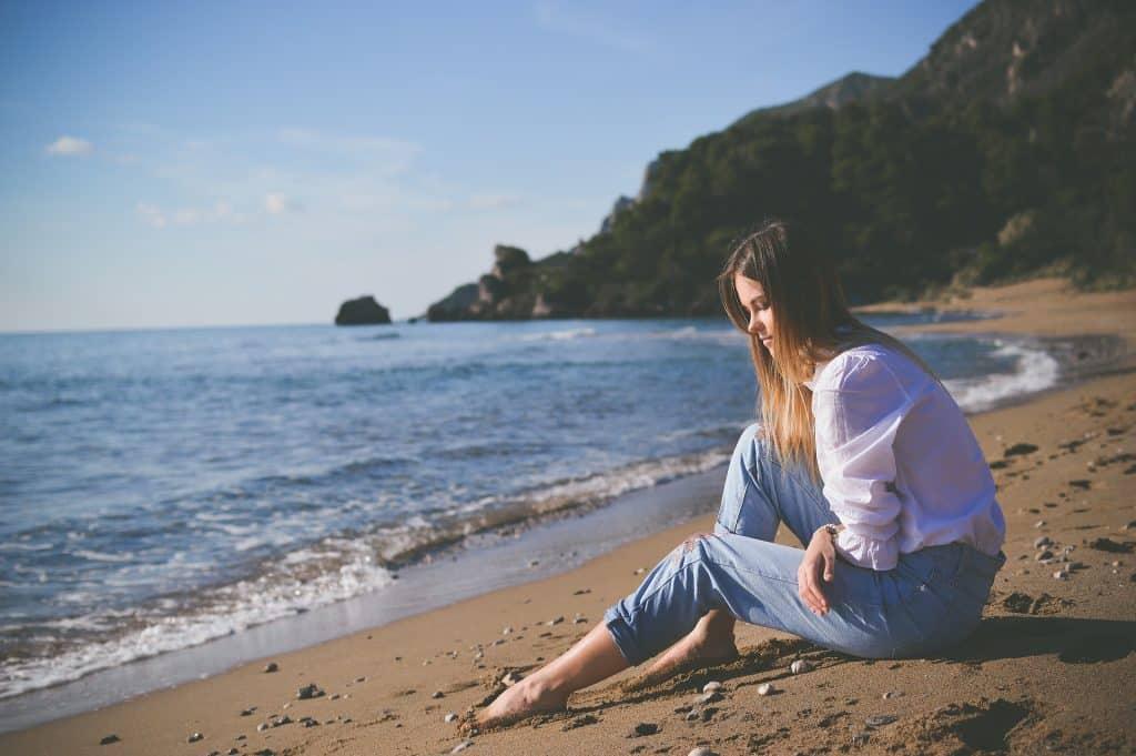 Imagem do mar e em destaque uma mulher de cabelos longos sentada pensativa na areia. Ela está usando calça jeans clara e uma camisa de manga longa na cor branca. Ela está triste e pensativa.