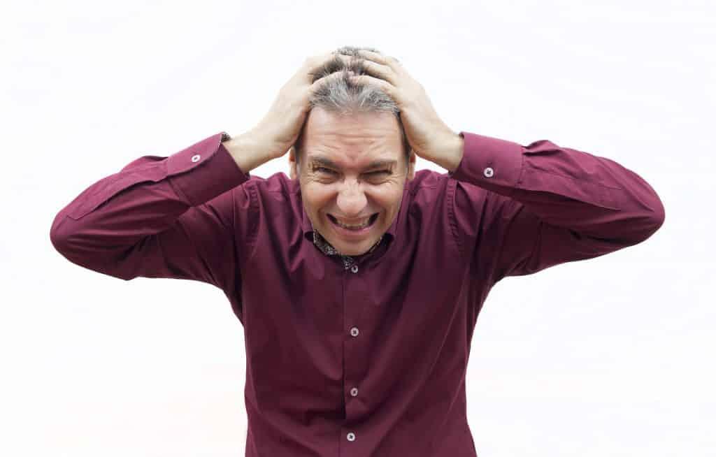 Imagem de um senhor estressado. Ele usa uma camisa na cor roxa e está com as duas mãos sobre a cabeça. Ele aparenta esta de mau humor.