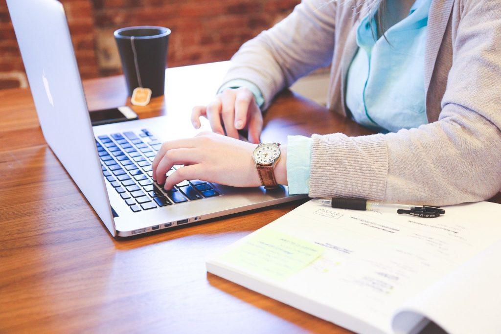 Imagem de uma mulher sentada à frente de um notebook trabalhando o. Ela usa uma blusa de frio aberta na cor bege e por baixo da blusa uma camisa na cor azul clara. Ao lado no note, uma caneca com chá.