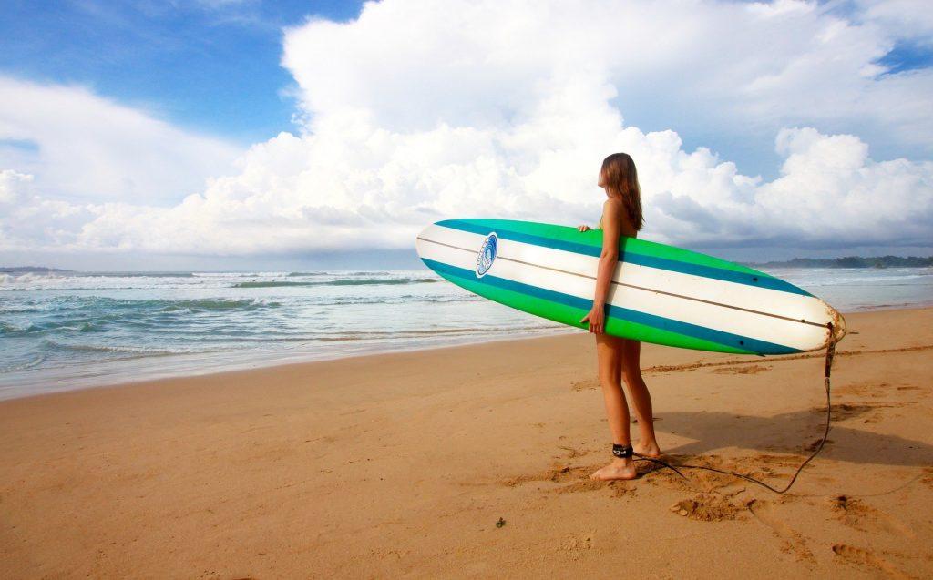 Imagem de uma praia e ao fundo um lindo mar azul. Uma mulher está na areia molhada olhando para o mar. Ela segura nos braços uma prancha de surfe.
