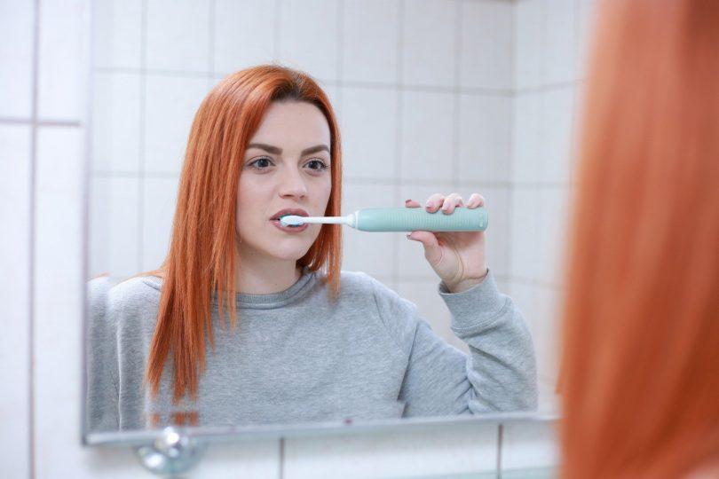 Imagem de uma mulher ruiva no banheiro escovando os dentes que estavam estragados.