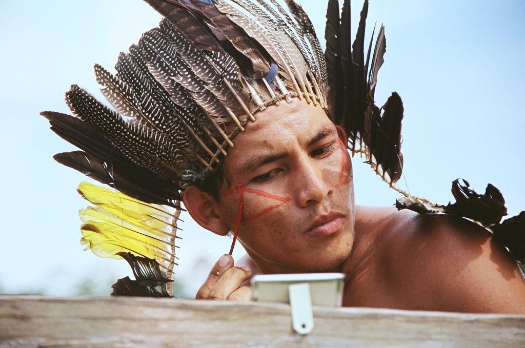 Imagem de um homem indígena usando um cocar com penas pretas e  amarelas. Ele está fazendo uma pintura em seu rosto - desenhando com tinta vermelha um triângulo. Ele está olhando para um pequeno espelho.