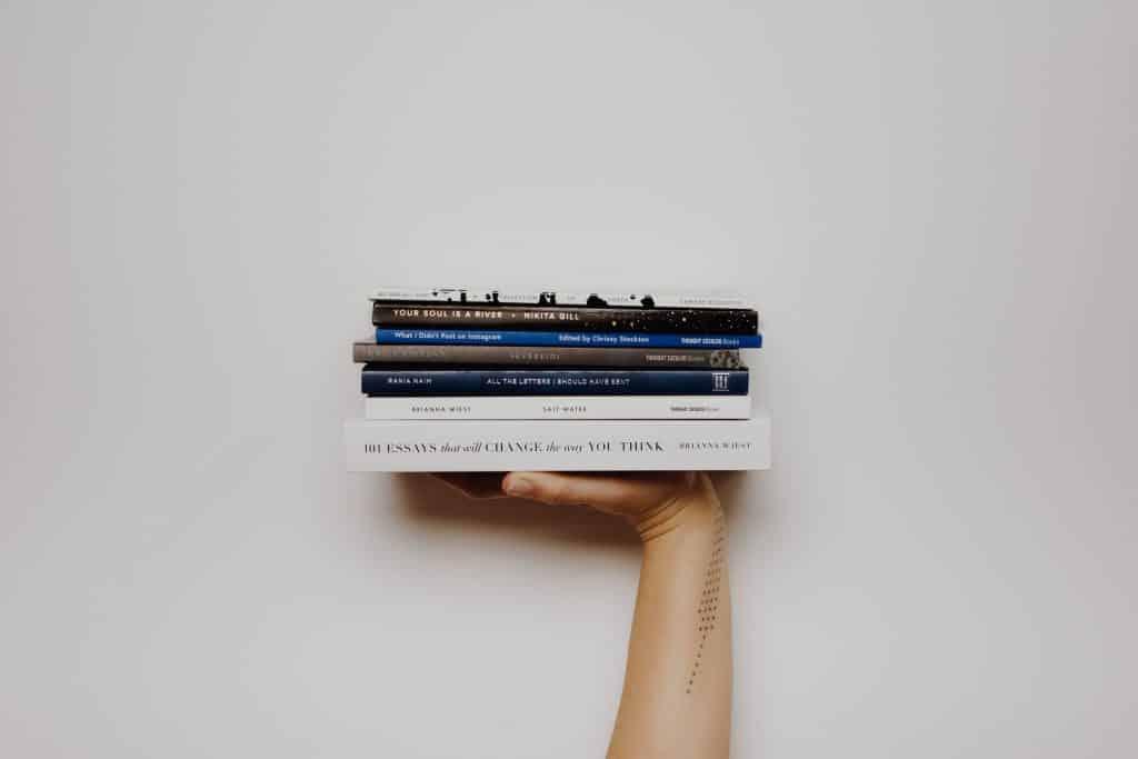 Pessoa segurando pilhas de livros