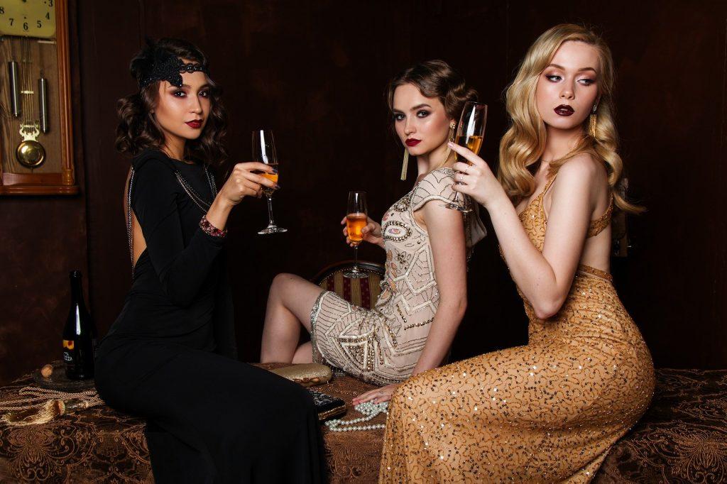 Imagem de três mulheres vestidas para uma festa e cada uma usa um modelo e cor de vestido diferente. As cores são preto, bege e dourado. Todas elas seguram uma taça com bebida e todas estão lindas e bem maquiadas e penteadas.