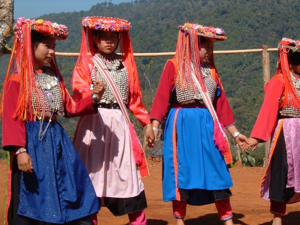 Imagem de quatro mulheres indígenas vestindo roupas coloridas e chapéus ornamentados com fitas e flores. Elas estão de mãos dadas em círculo, prontas para um dança no terreno da tribo.