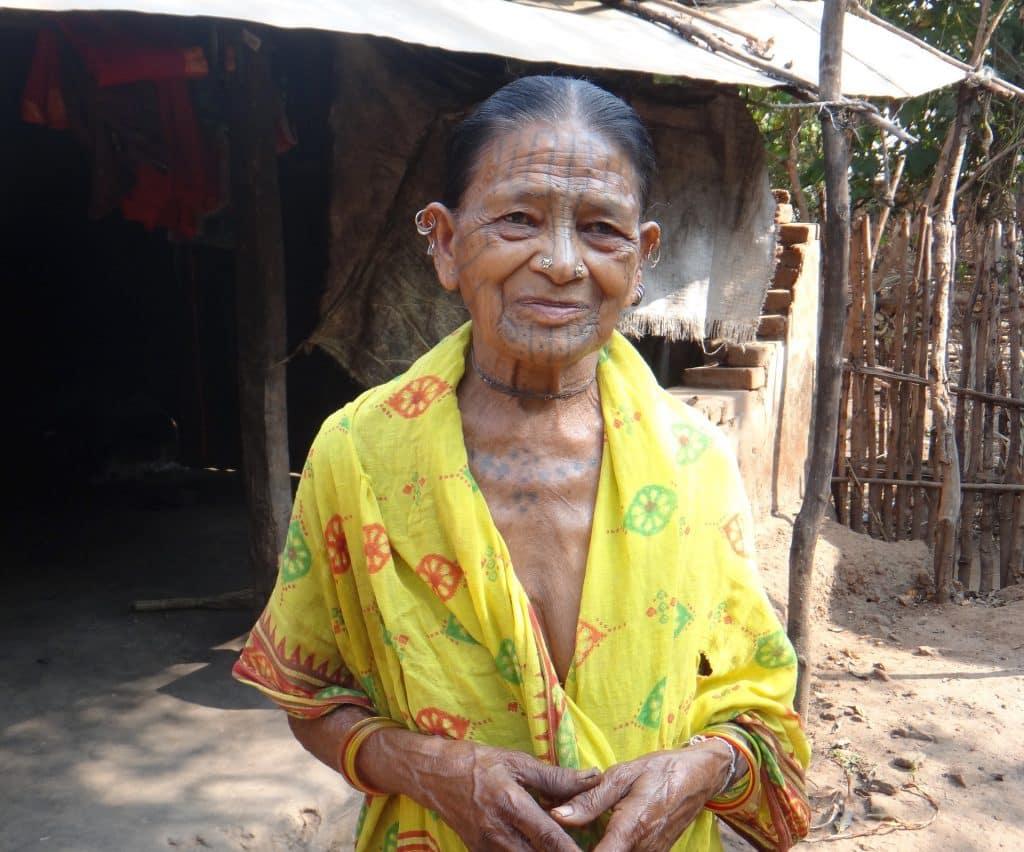 Imagem de uma senhora indígena com a pele toda do peito e do rosto desenhada com tinta azul - tatuagem tribal. Ela usa um lenço amarelo sobre o ombro, pulseiras coloridas e alguns brincos na orelha e no nariz.