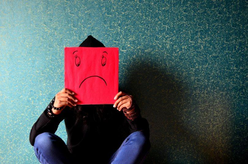 Imagem de fundo azul trazendo a figura de um homem sentado no chão. Ele segura entre as suas mãos e na frente do rosto uma placa vermelha onde está desenhando uma carinha triste.