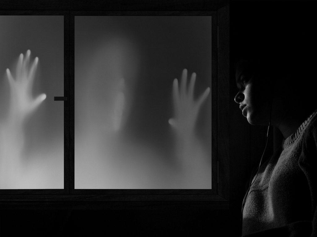 Imagem de uma assombração próxima à uma janela e uma mulher que estgá olhando para ela.