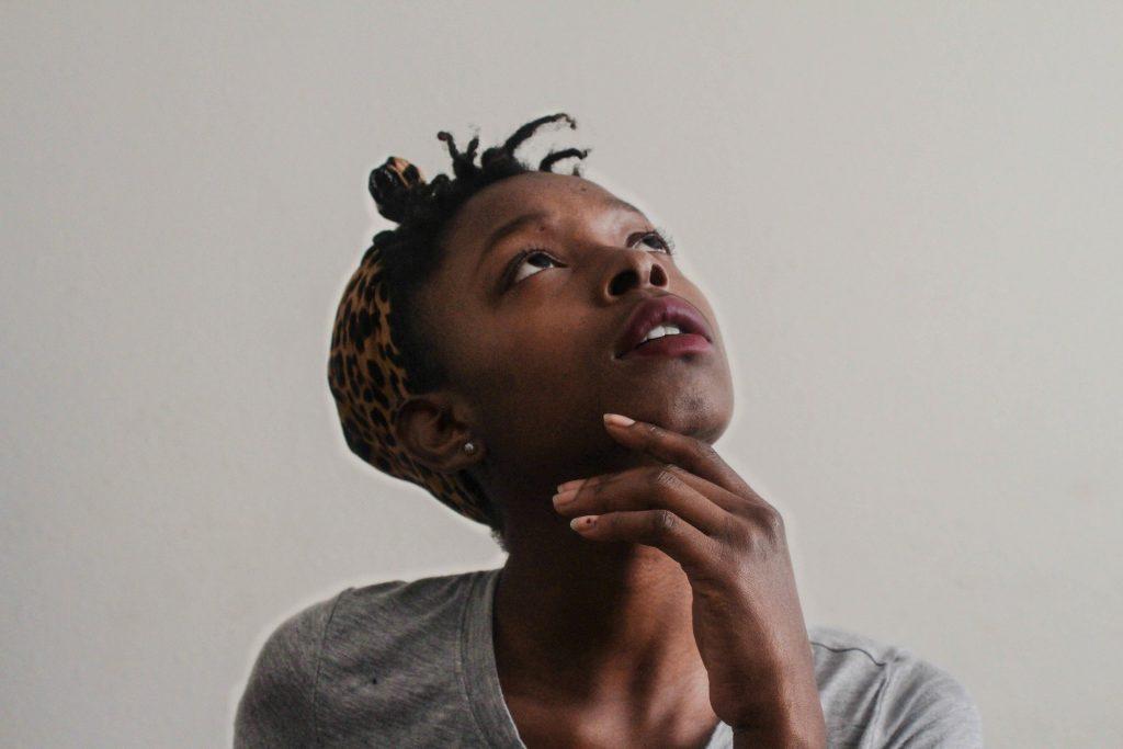 Imagem de uma mulher africana, olhando para o teto de forma pensativa. Ela usa uma camiseta cinza e um lenço animal print sobre a sua cabeça.
