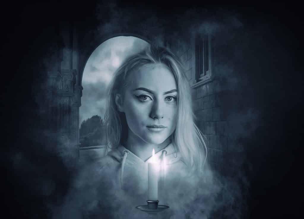 Imagem preta e branco de uma assombração mulher segurando uma vela acesa em suas mãos.