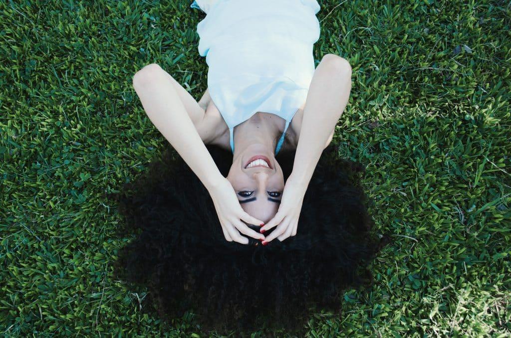 Imagem de um gramado bem verdinho e em destaque uma mulher deitada sobre ele. Ela usa camiseta regata branca e um grande e lindo cabelo ondulado e armado na cor preto.