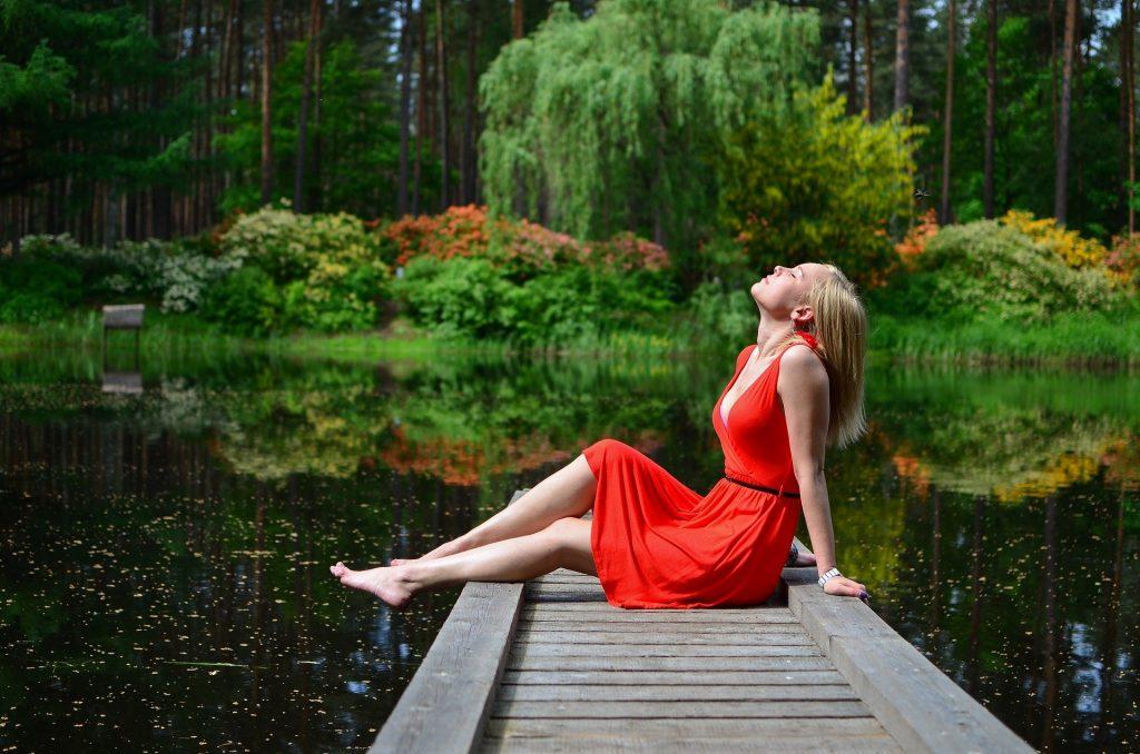 Imagem de um lago e ao fundo algumas árvores. Em destaque uma mulher loira sentada em uma peça de madeira sobre as águas desse lago. Ela usa um lindo vestido vermelho com um cinto fino preto.