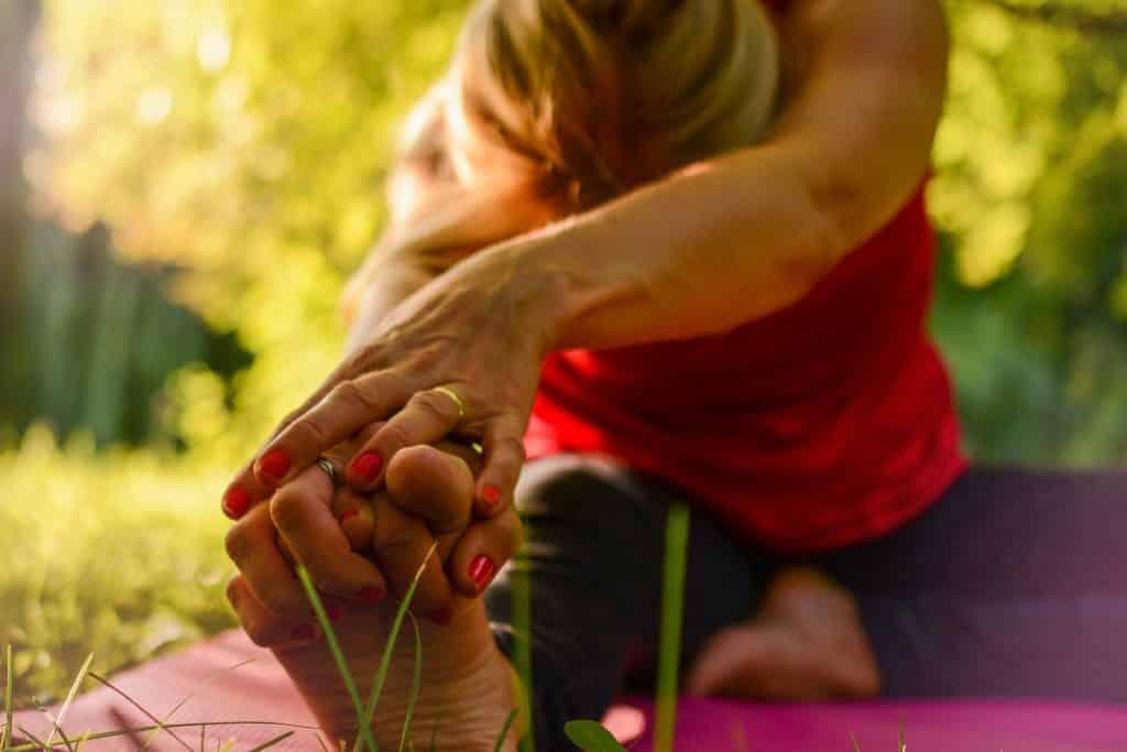 Imagem de uma mulher sentada em um tapete de ioga. Ela está fazendo alongamentos em uma praça bem arborizada.