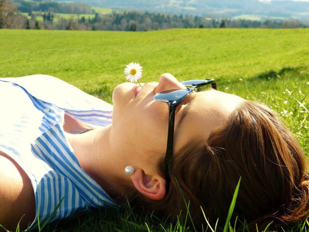 Imagem de  uma mulher deitada em um gramado. Ela usa óculos de sol, brinco de pérola branco e na sua boca ela traz uma pequena margarida.