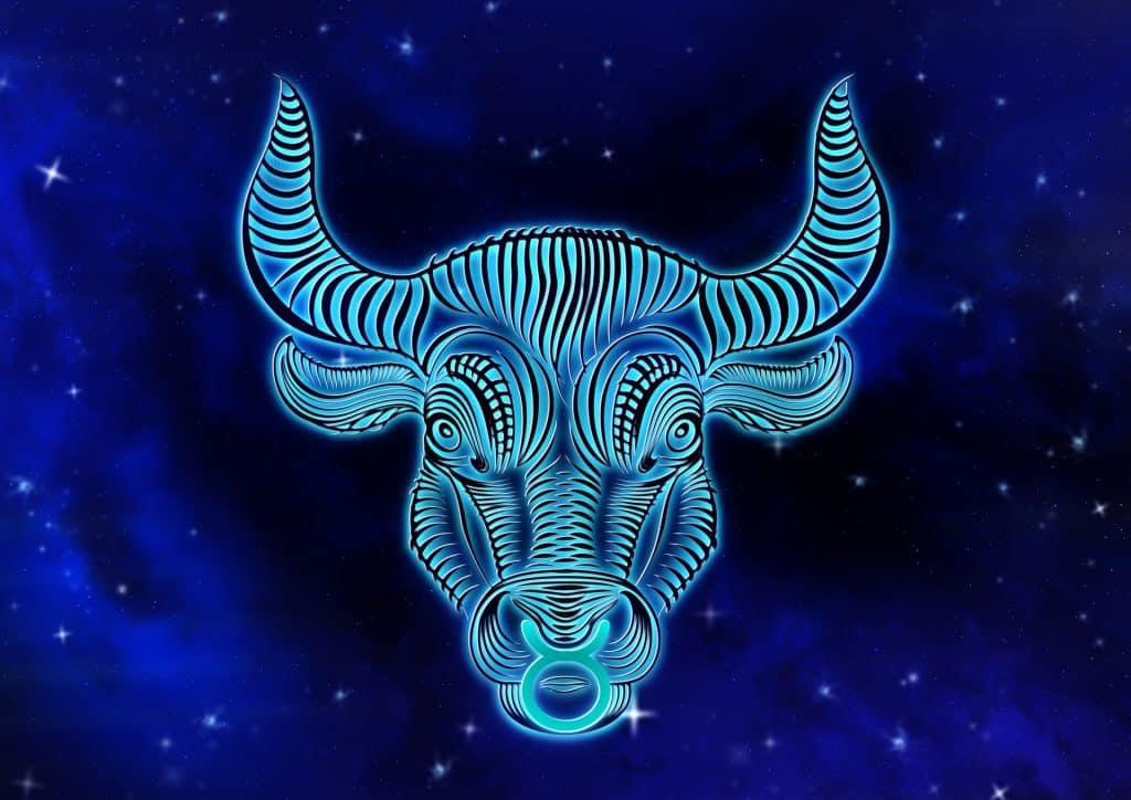 Imagem de fundo azul trazendo o símbolo do signo de touro, sendo representado pela face do touro.