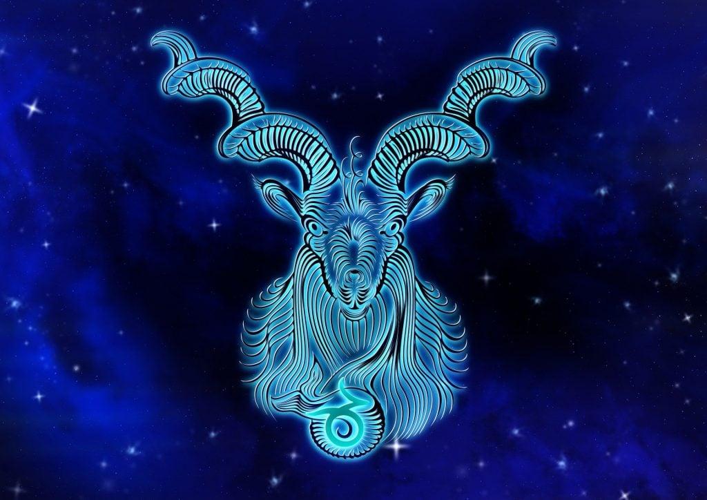 Imagem de fundo azul com alguns pontos de luz. Ao fundo a imagem de um animal mitológico denominado capricornus,  simbolizando o signo de capricórnio.