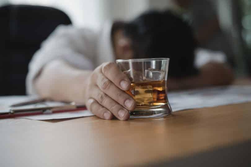 Homem deitado sobre uma mesa. Ele segura um copo de bebida alcoólica.
