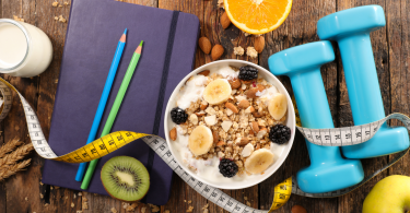 Foto representativa de uma dieta com banana e aveia em um pote ao lado de pesos, fita métrica e lápis