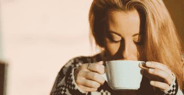 Mulher tranquila bebendo café de manhã