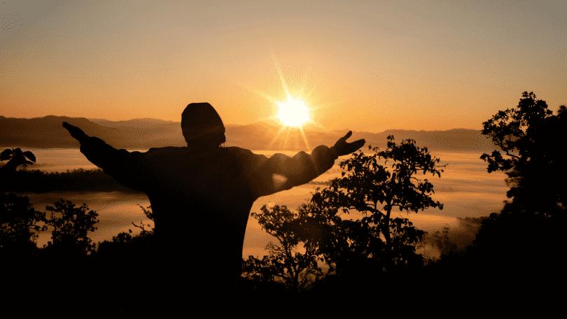 Silhueta de homem agradecendo com os braços erguidos durante por do sol