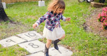 Garotinha brincando de amarelinha no quintal de casa