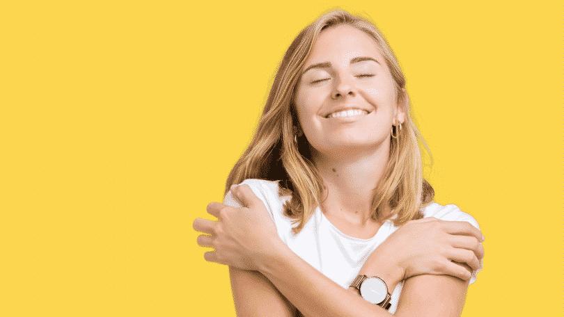 Mulher sorridente no funda amarelo se abraçando