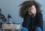 Garota deprimida com as mãos ao rosto sentada na sala