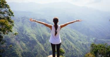 À beira de precipício, mulher com os braços erguidos.