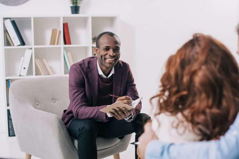 Terapeuta sorridente conversando com um jovem casal.