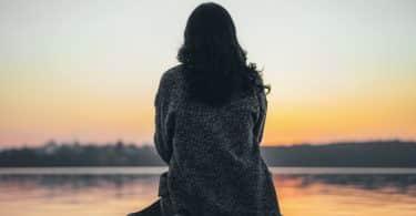 Mulher de cabelos castanhos sentada de costas num píer.