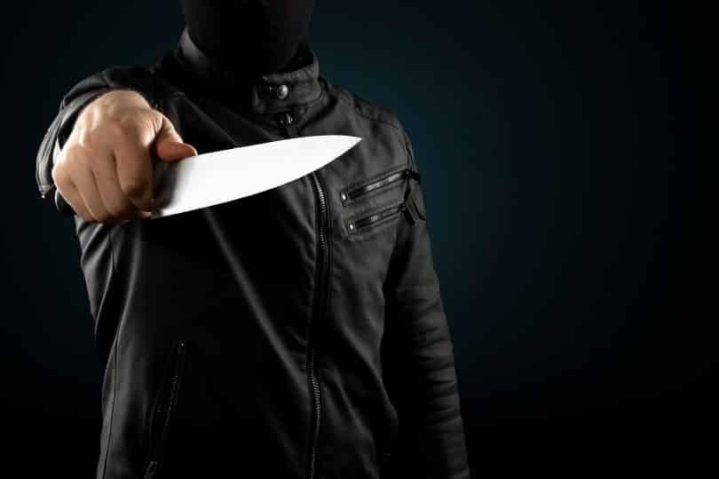 Homem mascarado segurando faca.