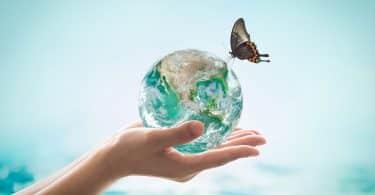 Mãos seguram planeta Terra representado por água. Há uma borboleta pousada nele.