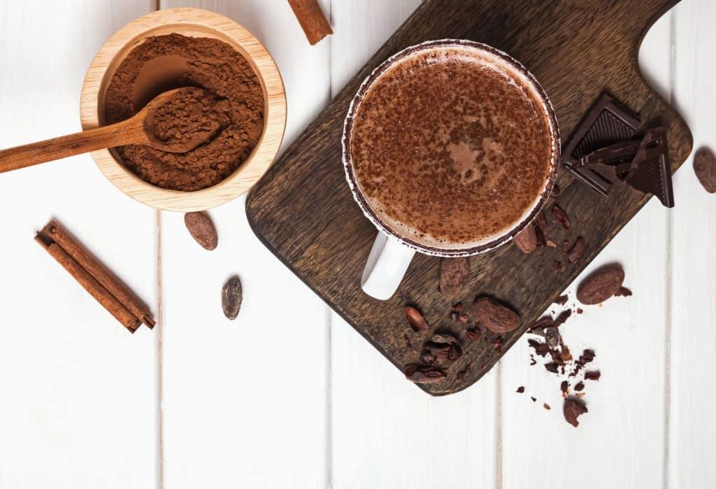 Xícara com chocolate em uma tabua com outros chocolates