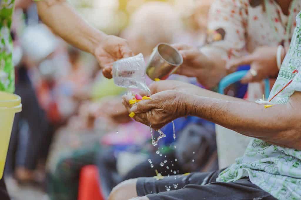Imagem de uma mulher de pé fazendo um benzimento nas pessoas idosas e que estão sentadas. Ela joga água nas mãos dessas pessoas.