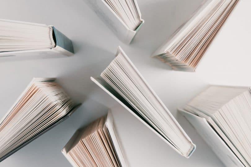 Livros posicionados pela base. Eles estão sobre uma superfície branca.