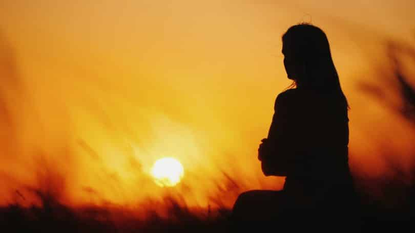Silhueta de mulher sentada em grama ao pôr do sol.