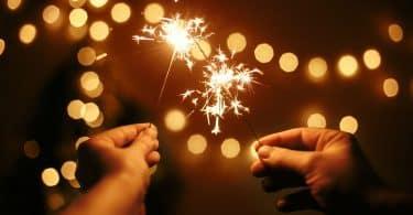 Mãos seguram duas velas estrela.