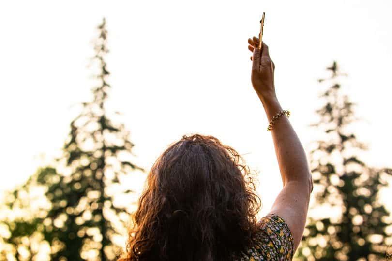 Mulher com a mão pra cima de frente para árvores