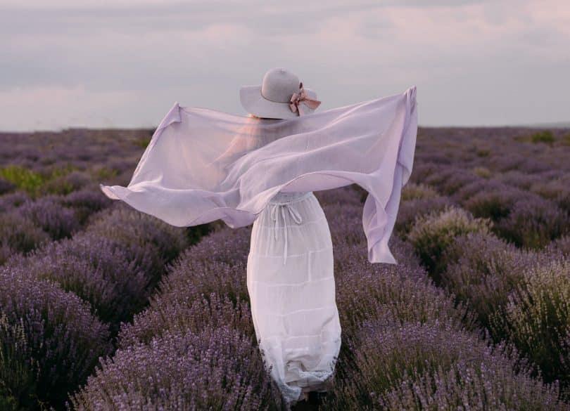 Mulher de costas usando vestido e lenço brancos, num campo de lavandas.