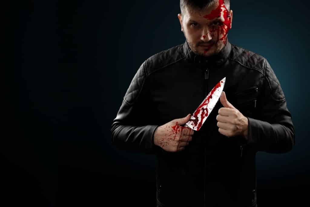Homem branco segurando faca com sangue fictício.