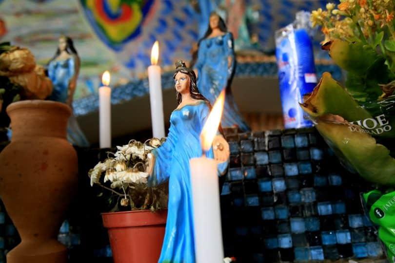 Imagem de um lindo altar com várias estátuas pequenas de Iemanjá, algumas velas brancas acesas e um vaso de flor branca.